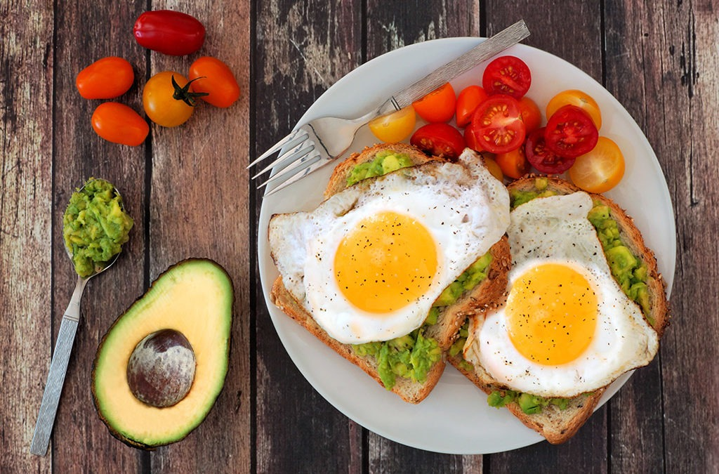 a plate of halved cherry tomatoes and two pieces of toast, each topped with mashed avocado and fried eggs