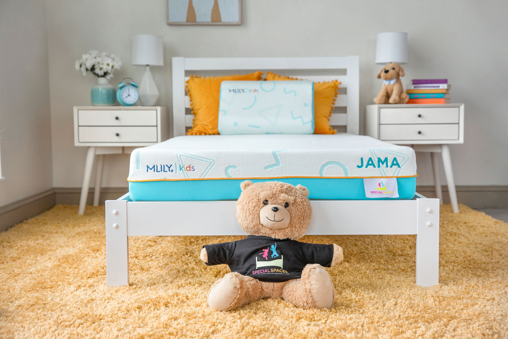 Kids' bedroom with MLILY JAMA mattress on a bed between two bedside tables with teddy bear at foot of bed.