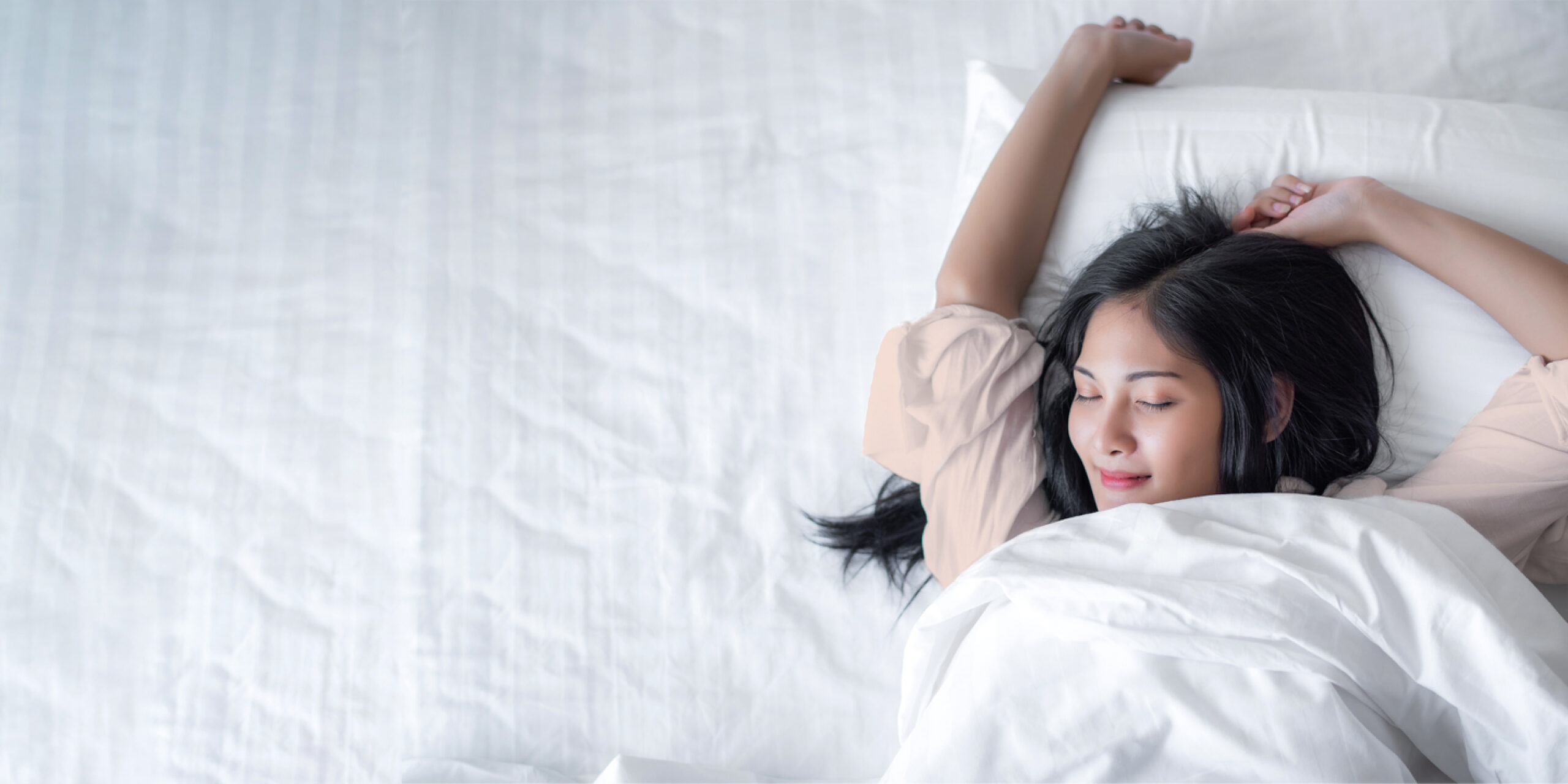 Woman with dark hair stretching arms above head while laying in bed with white bedding while wearing coral pajamas