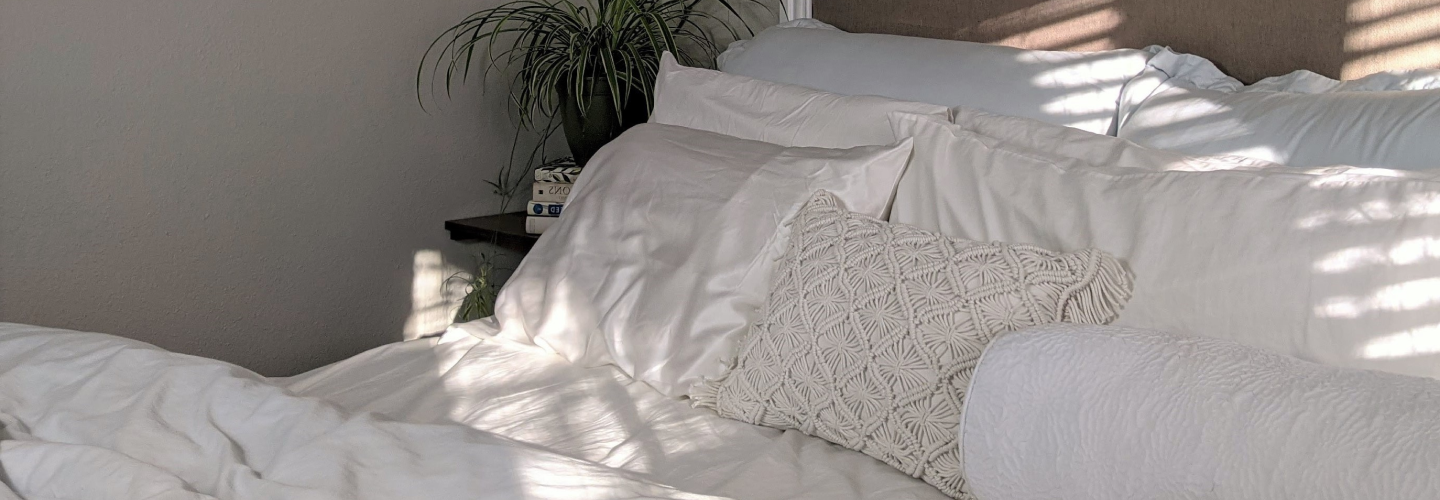 While MLILY pillows and bedding with dappled sunlight on the bed.